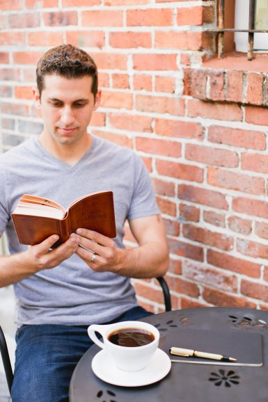 Jesus Calling brown small leathersoft being read by a man
