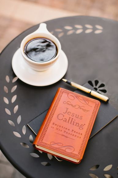 Jesus Calling small brown leather devotional on table with coffee