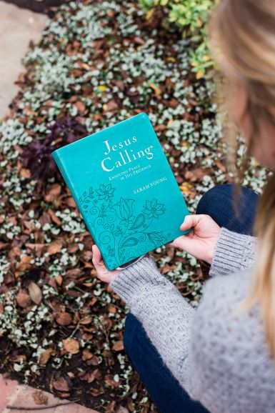 woman holding Jesus Calling large deluxe teal devotional