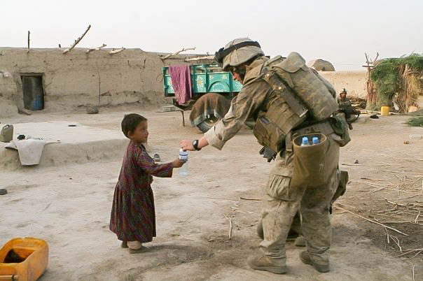 Zachary Bell giving water to a little girl in Afghanistan
