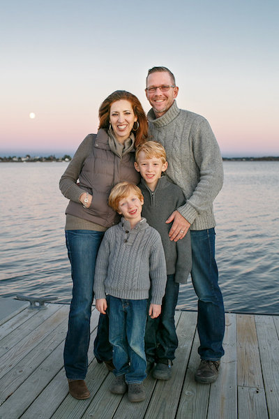 Maria-Jose Tennison with her husband and two sons standing on a dock at sunset.