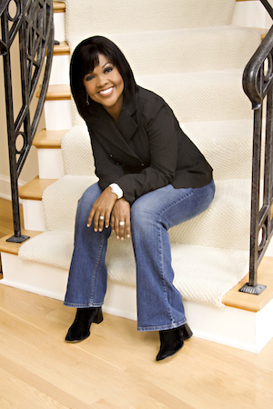 CeCe Winans seated on a staircase.