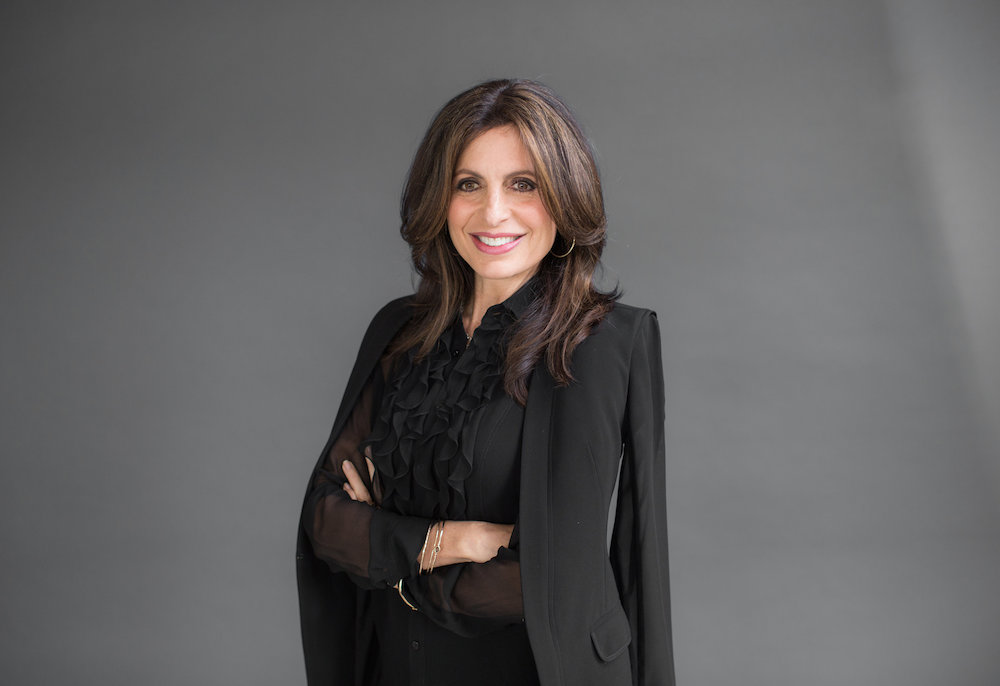 Lisa Bevere poses for a picture in a black suit.