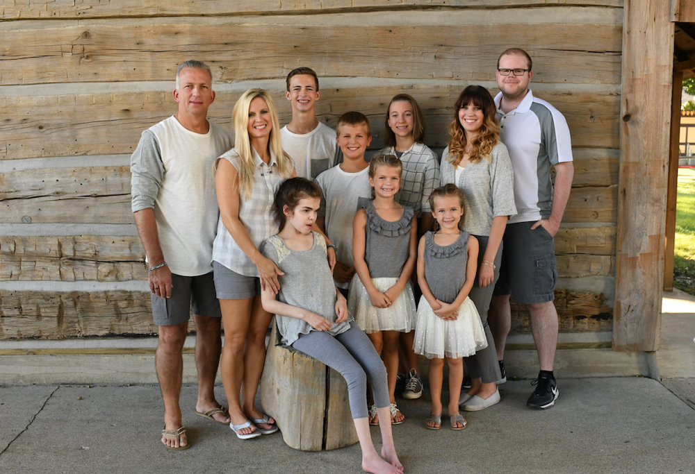 Rachel Wojo with her family in front of a wooden wall.