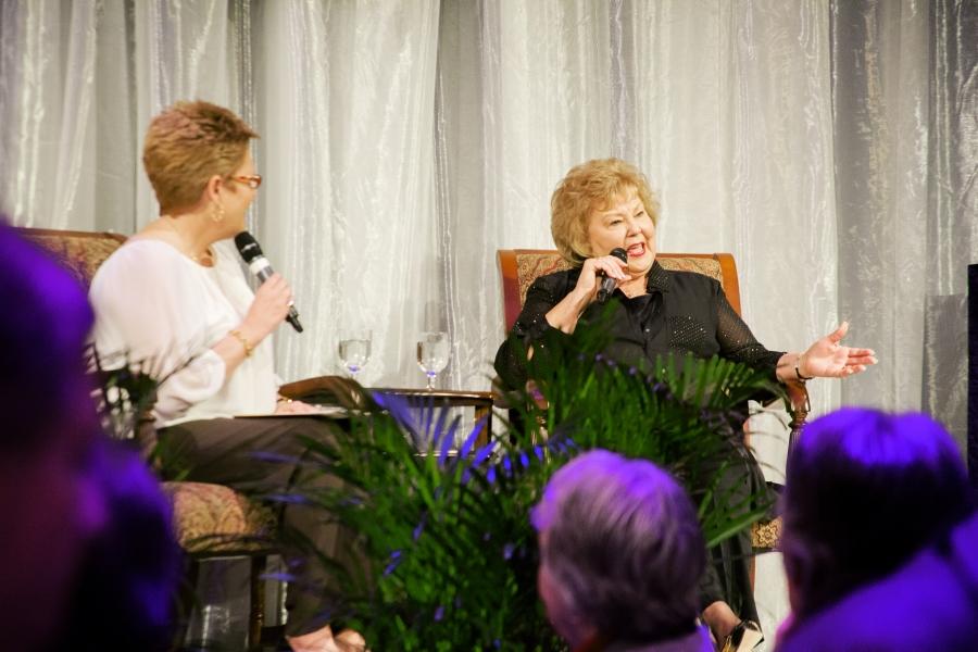 Gloria Gaithers speaking on stage.