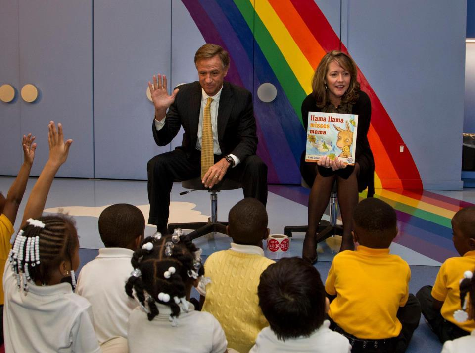 Bill and Crissy Haslam reading a story book to children.