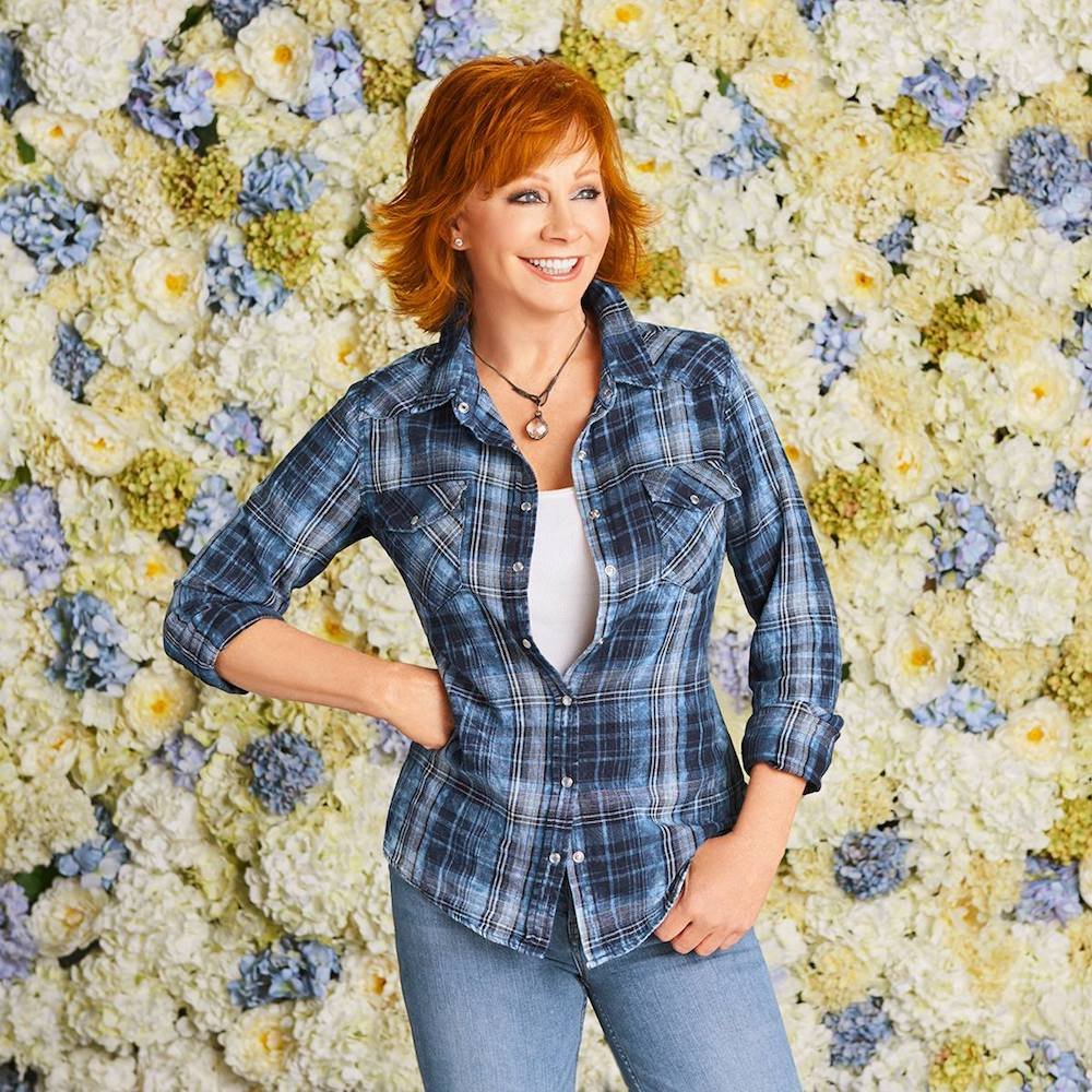 Singing Reba McEntire standing in front of a wall of flowers.