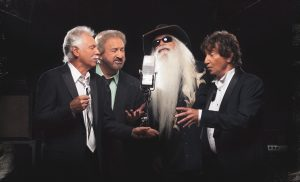 The Oak Ridge Boys press image singing around a single microphone