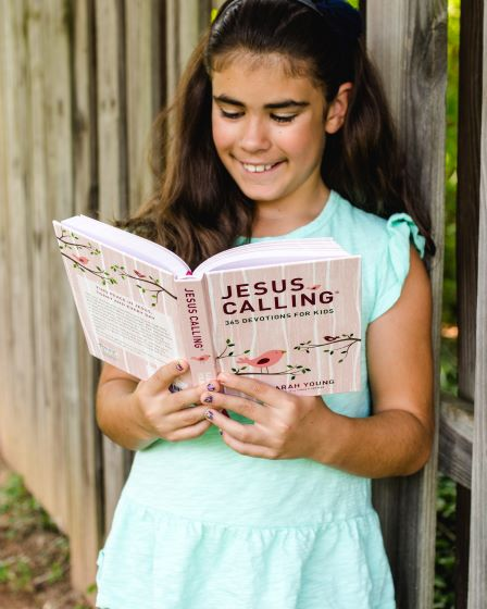 Girl reading Jesus Calling 365 devotions for kids pink edition