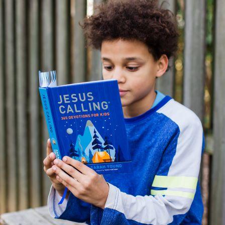 Boy reading Jesus Calling 365 devotions for kids blue edition