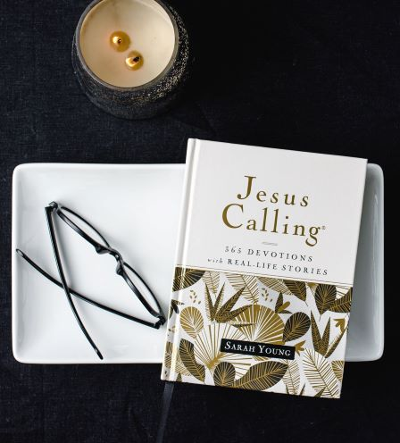 Jesus Calling with real life stories on table with candle and glasses