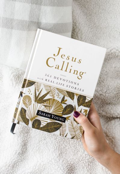a hand holding Jesus Calling with real life stories
