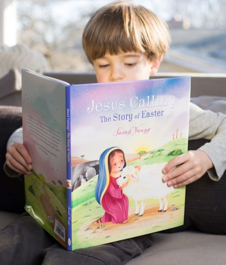 Little boy reading picture book of Jesus Calling The story of Easter